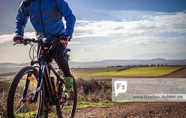 Nahaufnahme eines männlichen Mountainbikers  Radfahren auf einem Feldweg  Cagliari  Sardinien  Italien