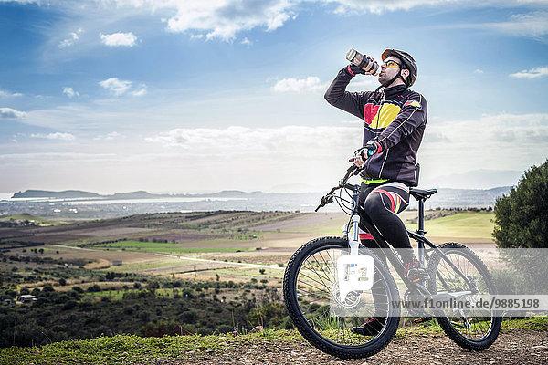 Männliche Mountainbiker Trinkflasche am Küstenweg  Cagliari  Sardinien  Italien