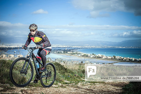 Mid adult male mountain biker on uphill coastal path  Cagliari  Sardinia  Italy