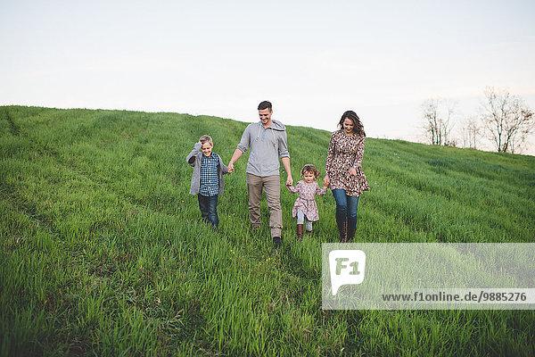 Eltern mit Sohn und Tochter beim Spaziergang im Grünen