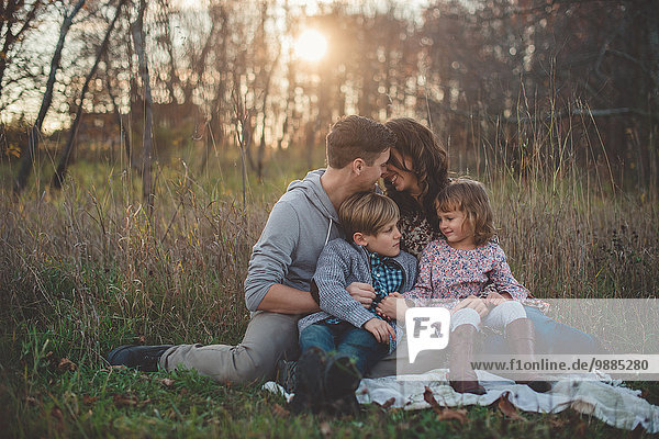 Young couple with son and daughter sitting on picnic blanket in field