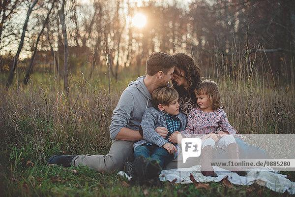 Junges Paar mit Sohn und Tochter auf Picknickdecke im Feld sitzend