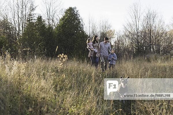 Junges Paar mit Sohn und Tochter beim Spaziergang mit dem Hund