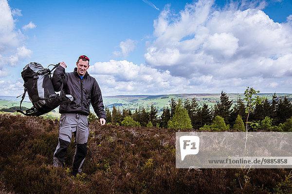 Männlicher Wanderer hebt Rucksack auf Schulter auf Heidemoor  Pateley Bridge  Nidderdale  Yorkshire Dales
