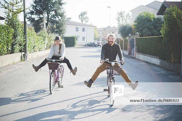 Junges Paar beim Radfahren mit ausgefahrenen Beinen