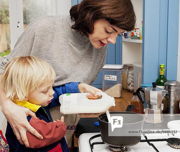 Mutter und Sohn gießen Milch in die Breipfanne in der Küche.