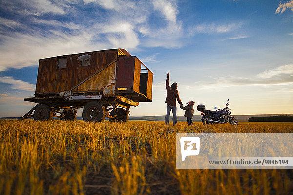 Vater und Sohn schauen bei Sonnenuntergang vom Herbstfeld auf  Dorf Sarsy  Gebiet Swerdlowsk  Russland
