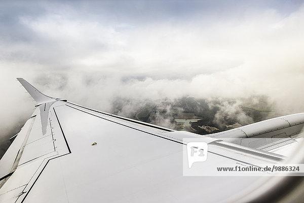 Blick auf Wolken und Flugzeugflügel über den Pyrenäen