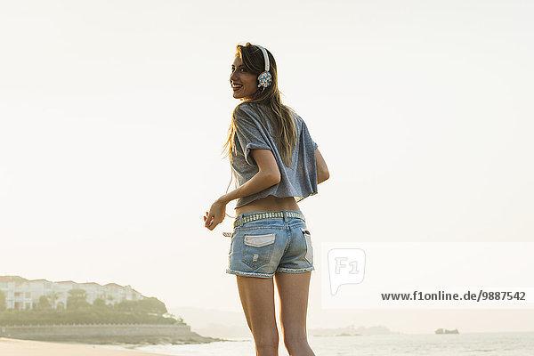 junge Frau junge Frauen zuhören Strand Kopfhörer Musik Klassisches Konzert Klassik