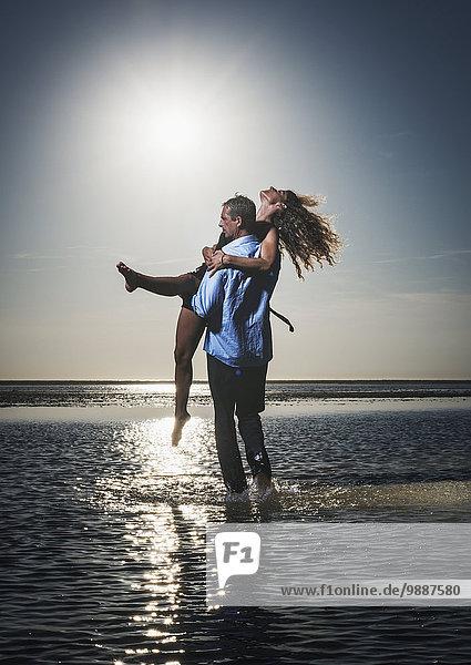 Wasser Frau Mann halten Ozean Küste seicht hinaussehen vorwärts