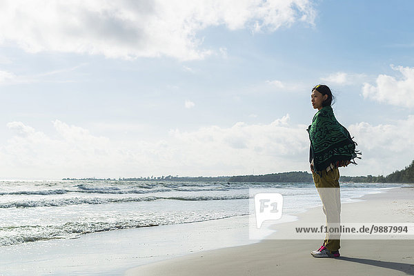 A young woman stands on Otres Beach looking out at the Gulf of Thailand; Sihanoukville  Cambodia