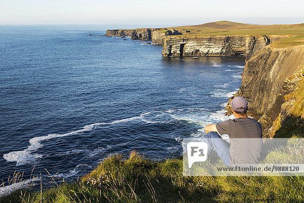 Felsbrocken sitzend Mann Ecke Ecken Sonnenuntergang Steilküste Küste dramatisch Ignoranz vorwärts Wiese Clare County Irland