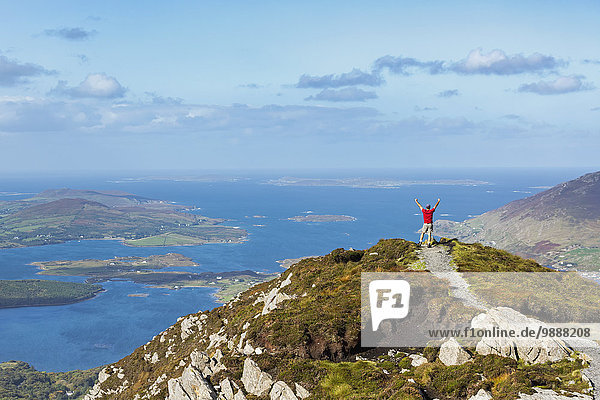 Male hiker with arms in the air on top of mountain overlooking the ocean with islands in the distance; Letterfrack  County Galway  Ireland