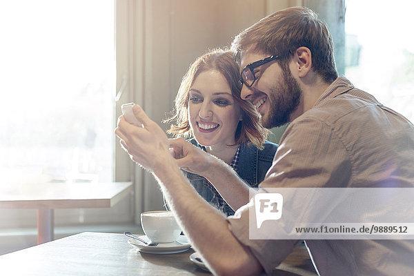 Paar mit Handy im sonnigen Cafe