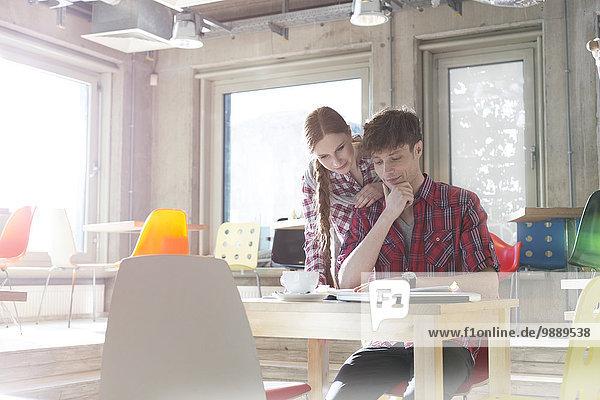 Kreative Geschäftsleute lesen im sonnigen Büro