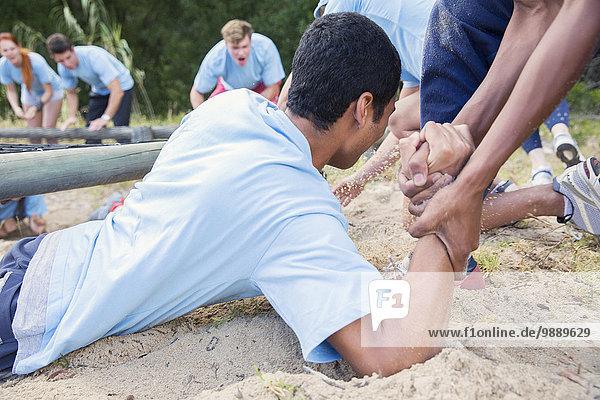 Teamkollege hilft Mann auf Boot Camp Kurs