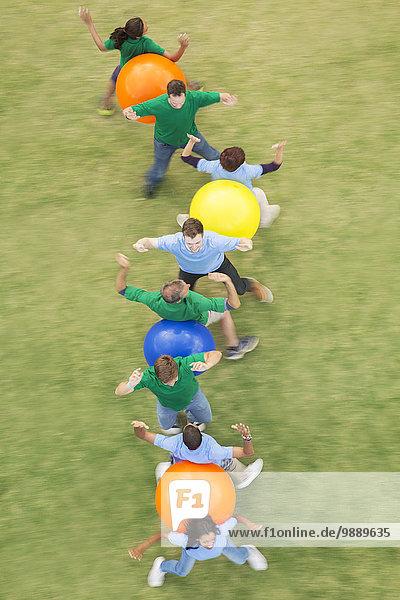 Mannschaftskameraden, die Fitnessball-Teambuilding-Aktivitäten durchführen