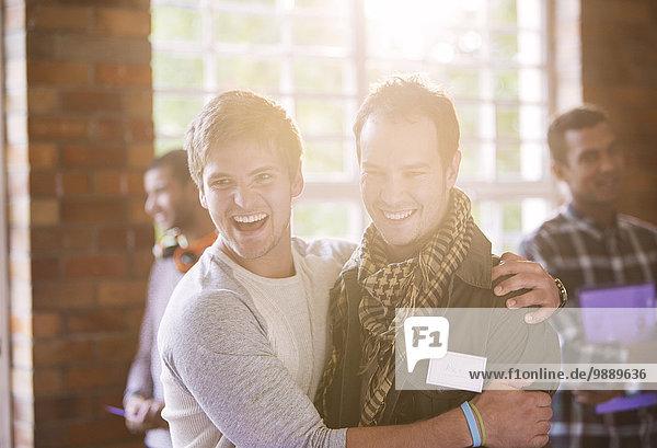 Lächelnde Männer umarmen sich beim Seminar