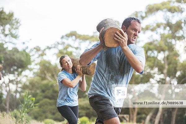 Mann und Frau laufen mit Baumstämmen auf dem Bootcamp-Kurs