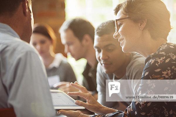 Geschäftsleute teilen sich ein digitales Tablett im Meeting
