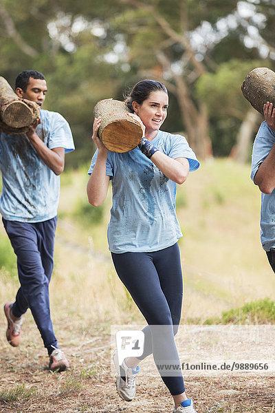 Frau läuft mit Logbuch auf dem Bootcamp-Hindernisparcours