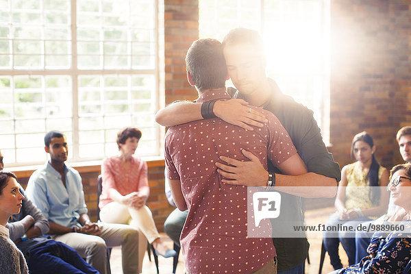 Männer  die sich bei der Gruppentherapie umarmen