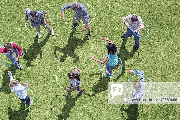 Menschen  die sich in Plastikbändern im sonnigen Gras drehen.