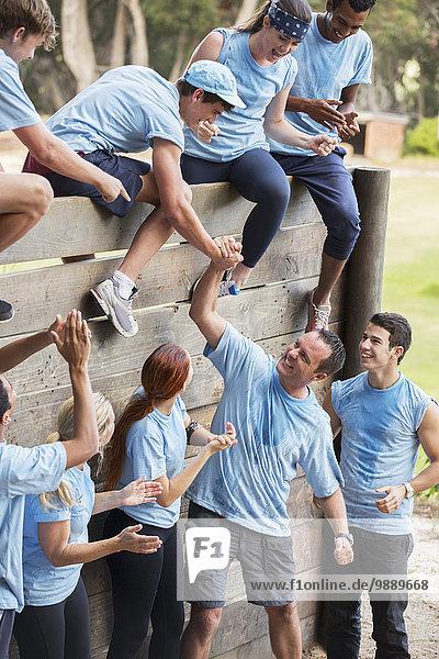 Teamkollegen helfen sich gegenseitig über die Wand auf dem Hindernisparcours des Bootcamps.