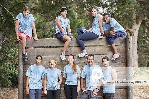 Porträt des selbstbewussten Teams an der Wand auf dem Bootcamp-Hindernisparcours