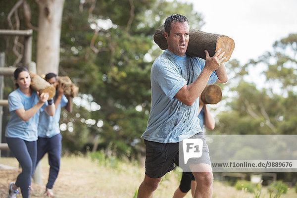 Entschlossener Mann beim Laufen mit Log auf dem Bootcamp-Hindernisparcours