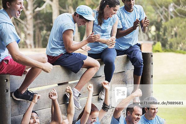 Jubelndes Team an der Wand auf dem Bootcamp-Hindernisparcours