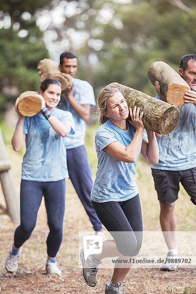 Entschlossene Leute  die mit Baumstämmen auf dem Bootcamp-Hindernisparcours laufen.