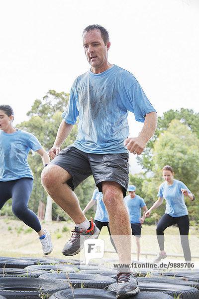 Entschlossener Mann beim Springen auf dem Hindernisparcours des Bootcamps