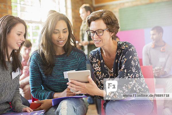 Frau zeigt Frauen im Gemeindezentrum digitales Tablett