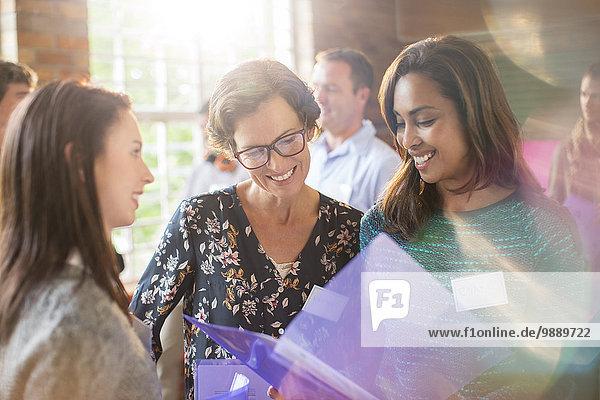 Lächelnde Frauen sehen sich den Papierkram im Gemeindezentrum an.
