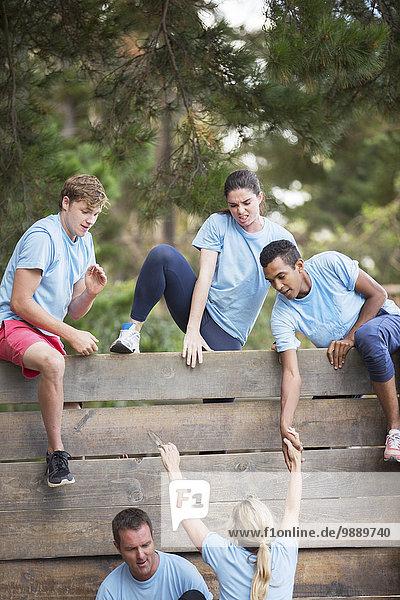 Mannschaftskameraden helfen der Frau über der Wand auf dem Hindernisparcours des Bootcamps