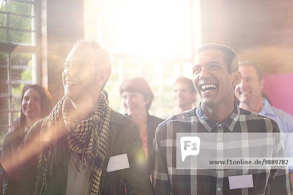 Lachende Männer im Publikum im Gemeindezentrum