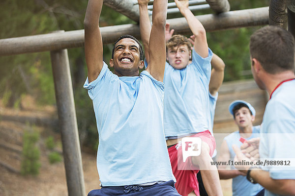 Entschlossene Männer  die auf Affenstangen auf dem Bootcamp-Hindernisparcours schwingen.