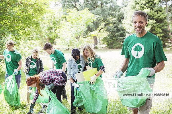 Porträt eines lächelnden Umweltschützers  der Müll aufsammelt.