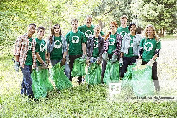 Porträt von lächelnden Umweltschützern  die Müll aufsammeln