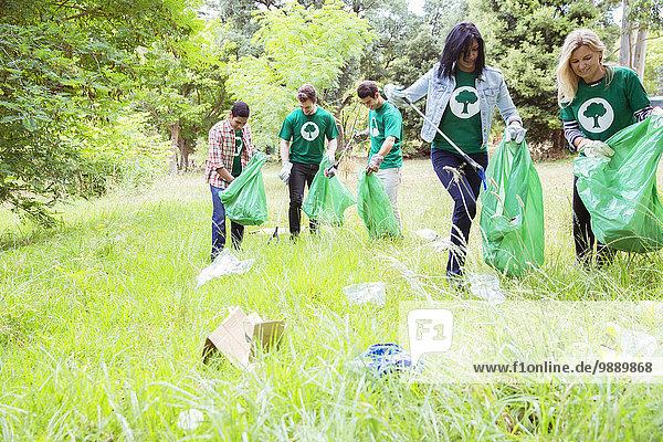 Freiwillige Umweltschützer sammeln Müll auf dem Feld ein