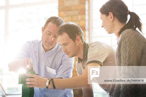 Geschäftsleute stapeln grüne Blöcke im sonnigen Büro
