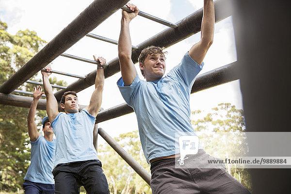 Entschlossene Männer beim Überqueren von Affenstangen auf dem Bootcamp-Hindernisparcours