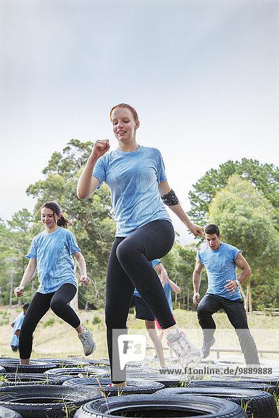 Entschlossene Frau beim Springen auf dem Hindernisparcours des Bootcamps
