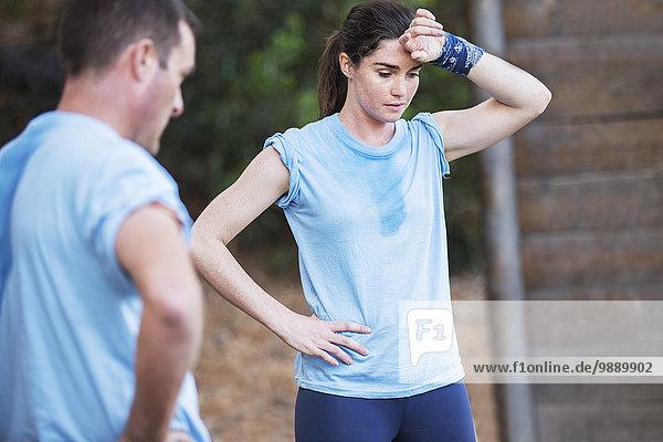 Müde Frau ruht auf dem Bootcamp-Hindernisparcours