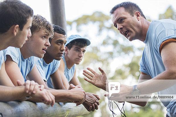 Teamleiter motivierendes Team im Bootcamp-Hindernisparcours