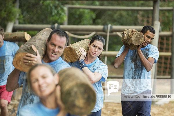 Ermitteltes Team mit Baumstämmen auf der Boot Camp Rennstrecke