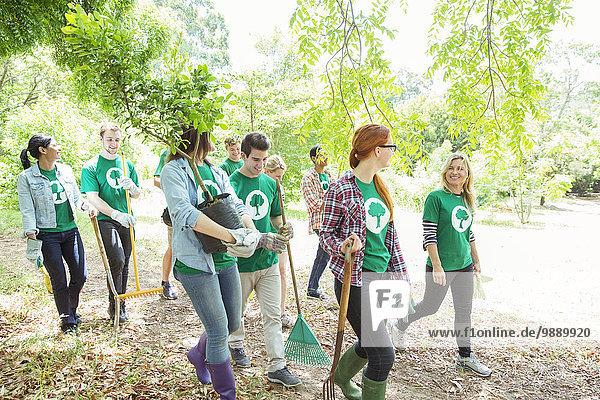Lächelnde Umweltschützer pflanzen neuen Baum