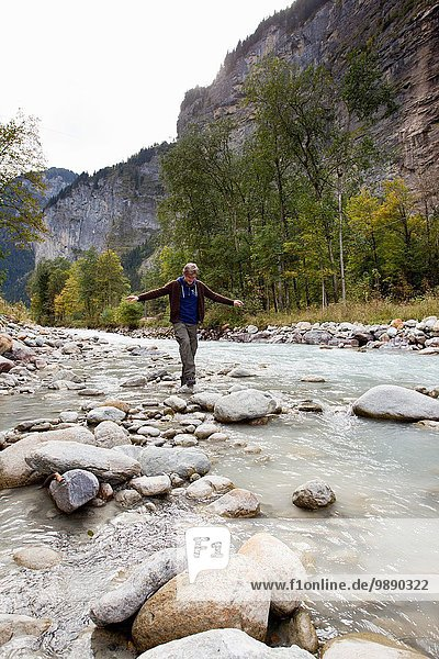 Male hiker stepping over rocks in river  Grindelwald  Switzerland