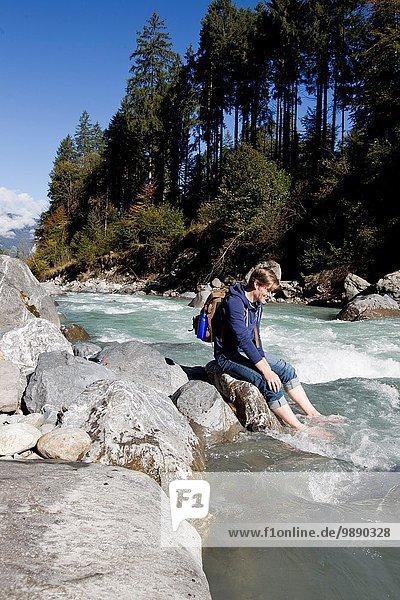 Male hiker sitting on rock with bare feet in river  Lauterbrunnen  Grindelwald  Switzerland